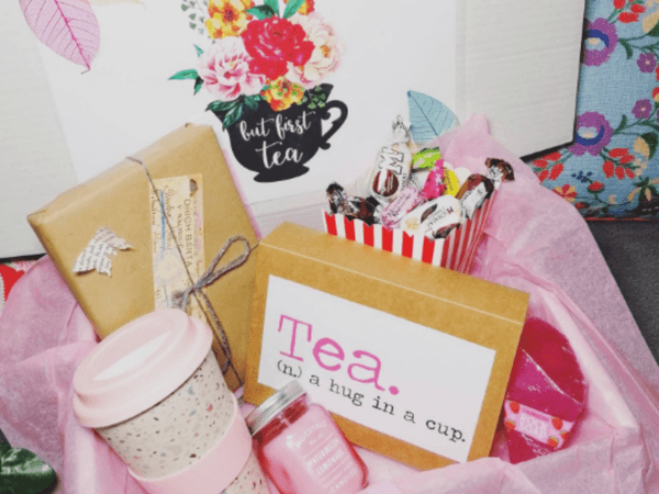 flask, candle, book and tea packs in a box